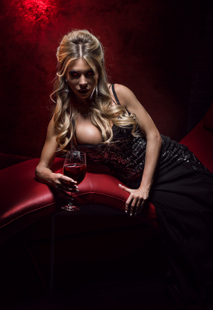 vamp: Sexy woman vampire in black dress with glass of red wine