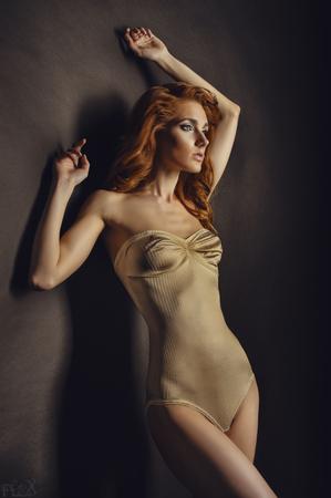 piel humana: mujer de pelo rojo en color beige posando traje sobre fondo gris de la pared Foto de archivo