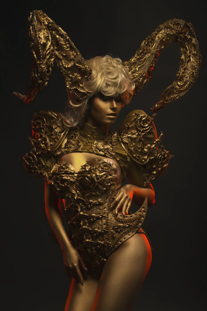 peo: Beautiful devil women with golden ornamental horns on dark background Stock Photo