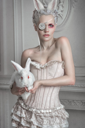 Portrait of a girl in a whight costume holding a white bunny