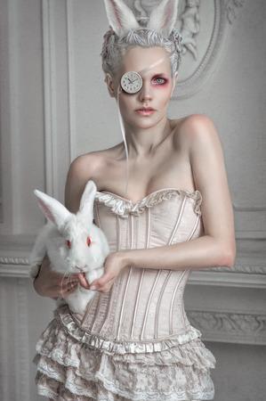 Ritratto di una ragazza in un costume whight possesso di un coniglio bianco