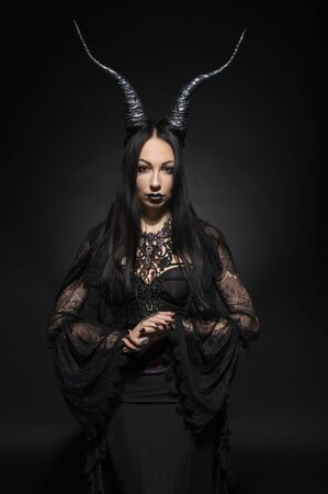 fema: Young woman in black fantasy costume with big horns on dark background Stock Photo
