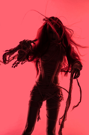 mummification: Silhouette of young mummy woman in bandage on pink background