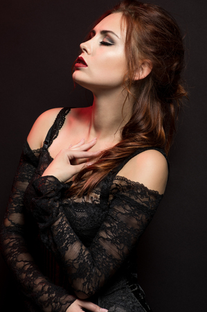 pers: Young woman in black gothic costume on dark background Stock Photo