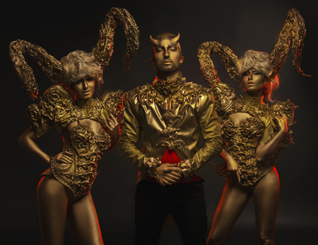 peo: Beautiful devil women with golden ornamental horns and handsome devil man in ornamental jacket on dark background