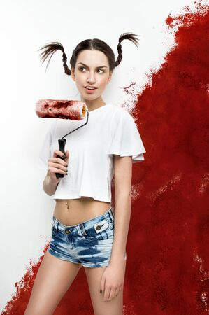 Young beautiful Girl painting the walls into bloody red color Фото со стока