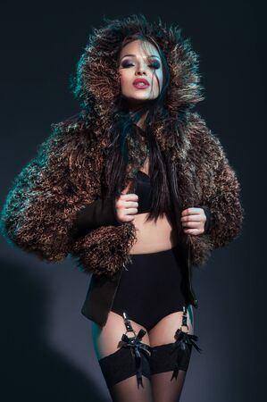 Young beautiful woman in black sexy lingerie and furry coat