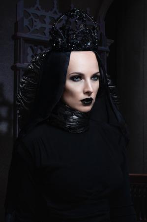 Dark queen in black fantasy costume on dark gothic background