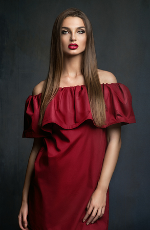 Young lady in red dress Фото со стока