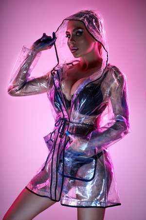 Woman in lingerie and transparent raincoat
