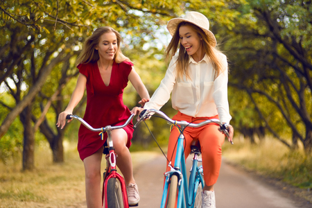 Beautiful sisters riding bicycles in park Stock Photo