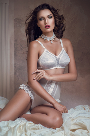 Beautiful woman in white lingerie sitting on bed and posing