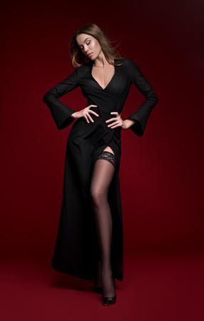 Hermosa mujer en vestido negro y medias posando en la cámara sobre fondo rojo