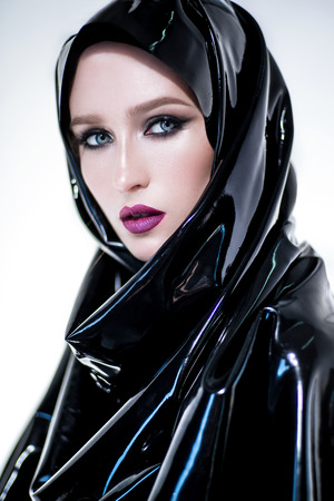 Woman with oriental makeup and black latex hijab on the white background