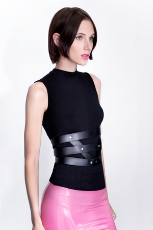 Young woman in pink latex skirt with leather accessories posing at camera