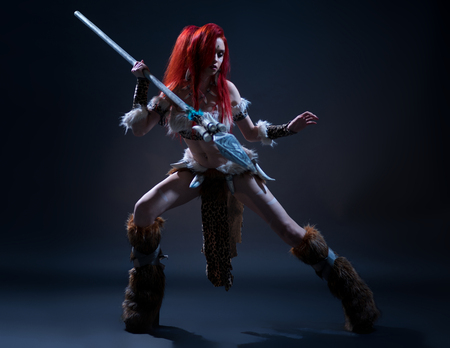Beautiful red haired woman in stone age clothing with spear posing at camera on dark background Stock Photo