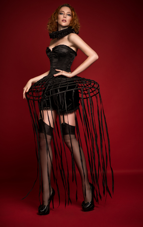Woman in black corset, skirt with stripes, frill and stockings posing at camera against red background