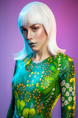 Portrait of young pretty blonde woman in green outfit posing at camera against colorful background