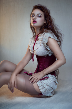 Beautiful woman in white lace and red corset sitting on floor and posing at camera