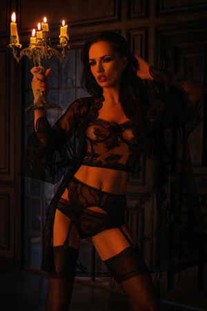 Brunette woman in black lace lingerie with candelabrum posing on dark background Stockfoto