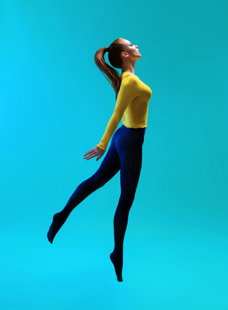 Side view of woman with ponytail wearing yellow jumper and blue leggings jumping on blue background 免版税图像