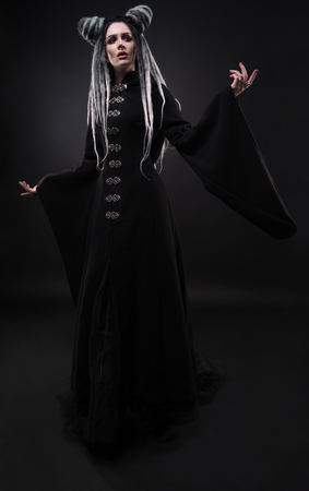 Full length view of woman with dreads wearing black gothic coat and posing on dark background