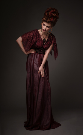 Full length view of woman with baroque hairstyle and evening maroon dress posing on dark background