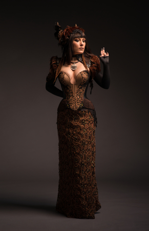 Full length view of brunette woman in gothic steampunk gown posing at camera