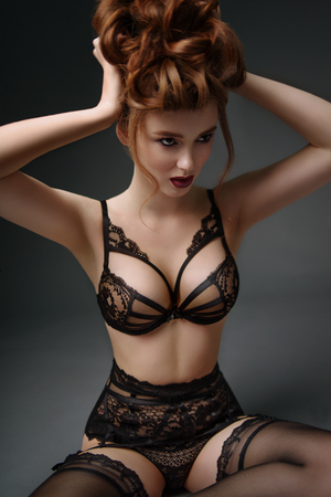 Portrait of woman with baroque hairstyle and fancy lace lingerie posing on dark background