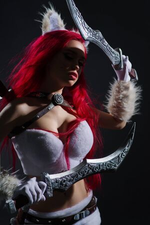 Sexy redhead woman in cosplay costume of warrior cat with swords posing on dark background Stock fotó