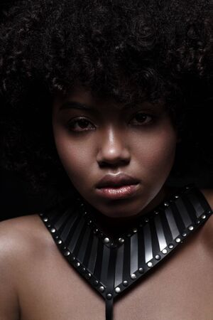 Beautiful african american nacked woman with curly hairstyle wearing leather necklace with metal inserts on black background Фото со стока