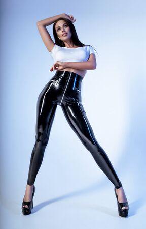 Sexy brunette woman in white top and vinyl leggings posing on light studio background Archivio Fotografico