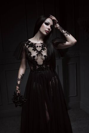 Beautiful brunette woman with gothic makeup wearing stylish black dress and posing on grey background