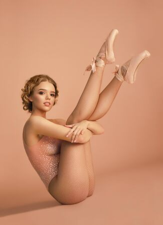 Beautiful ballerina in shiny body and pointe shoes posing on beige background 写真素材
