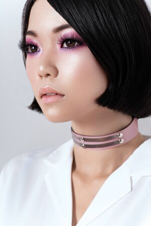 Portrait of seductive brunette asian woman in pink choker and white shirt