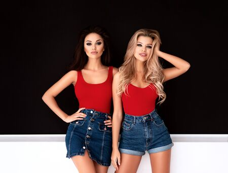 Blonde and brunette models in red singlets with denim skirt and shorts posing near blackboard in studio