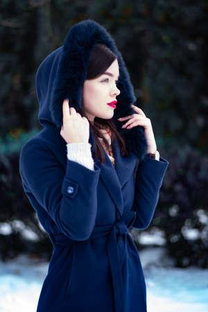Young beautiful woman walking on street in winter