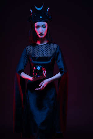 Brunette model in gothic black outfit posing with skull in studio
