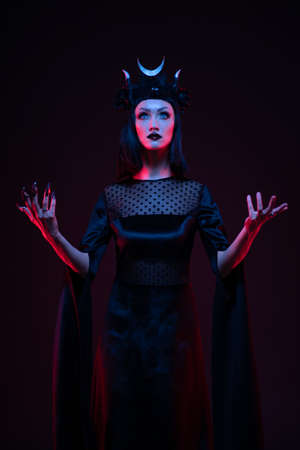 Portrait of gothic woman in balck clothes posing in studio on dark background