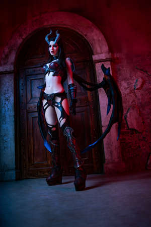 Girl devil in gothic costume and wings posing next to the brick wall