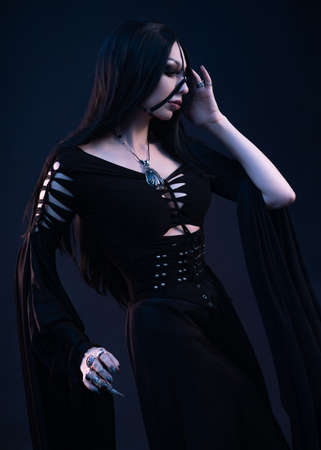 Young woman in black dress in Gothic style posing in studio 免版税图像