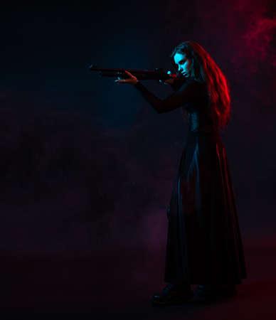 Longhair vampire in black long corset dress in smoke holding a gun 免版税图像