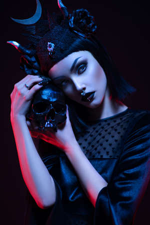 Young woman in black dress in Gothic style posing with skull