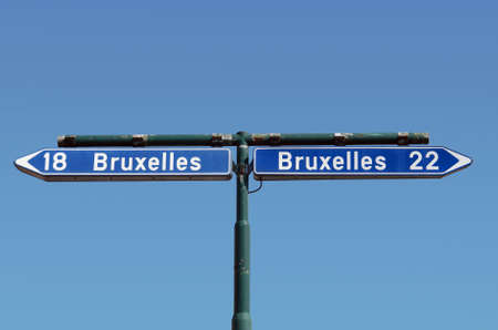 either: Ambiguous road sign on a crossroad in Belgium. Concept of confusion and contradiction, choice and dilemma. Stock Photo