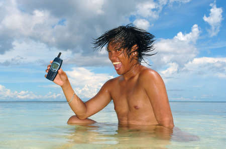 Asian boy in a tropical sea advertising a cell-phone under a majestic cloud-scape. Concept of enthusiasm and sales for an unusual service. Marketing an outstanding product. photo