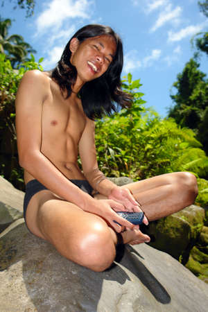 Asian longhaired boy posing and using cell-phone in a tropical jungle setting. Tarzan and jungle-boy concept. photo