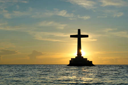 Colorful sunset over Sunken Cemetery on the tropical island of Camiguin. The cross in the sea is a memorial for the victims of the 1871 volcanic eruption here, when the ancient capital Cotta Bato was destroyed by the lava. Stock Photo