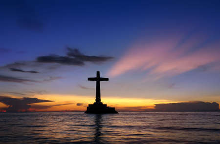 touristy: Colorful sunset over Sunken Cemetery on the tropical island of Camiguin. The cross in the sea is a memorial for the victims of the 1871 volcanic eruption here, when the ancient capital Cotta Bato was destroyed by the lava. Stock Photo