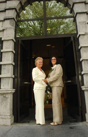 レズビアン熟女カップル、公式の結婚式の後の市庁舎の前でポーズします。同じ結婚はベルギーで完全に合法です。