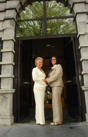 lesbiana: Pares maduros lesbianos que se presentan delante de pasillo de ciudad despu�s de la ceremonia oficial de la uni�n. la uni�n del Mismo-sexo es completamente legal en B�lgica.